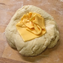 Faire un petit creux au centre du pâton et disposer le fromage